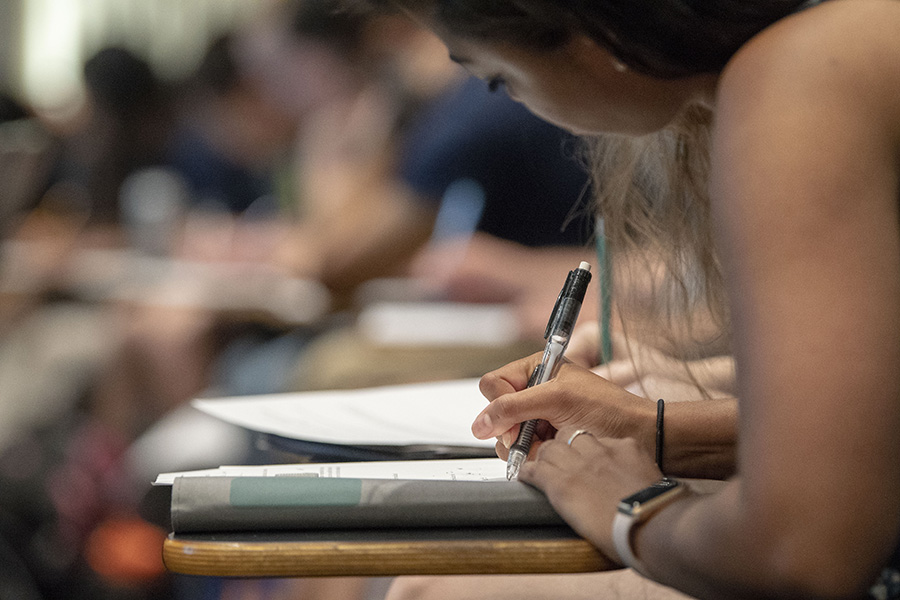 A student writes down notes during a class lecture.